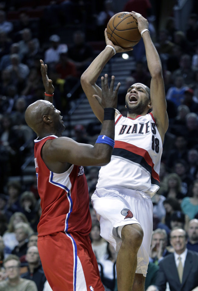 Portland Trail Blazers forward Nicolas Batum, right, from France, shoots over Los Angeles Clippers forward Lamar Odom during the second half of an NBA basketball game in Portland, Ore., Saturday, Jan. 26, 2013.  Batum scored 20 points as the Trail Blazers defeated the Clippers 101-100. (AP Photo/Don Ryan)