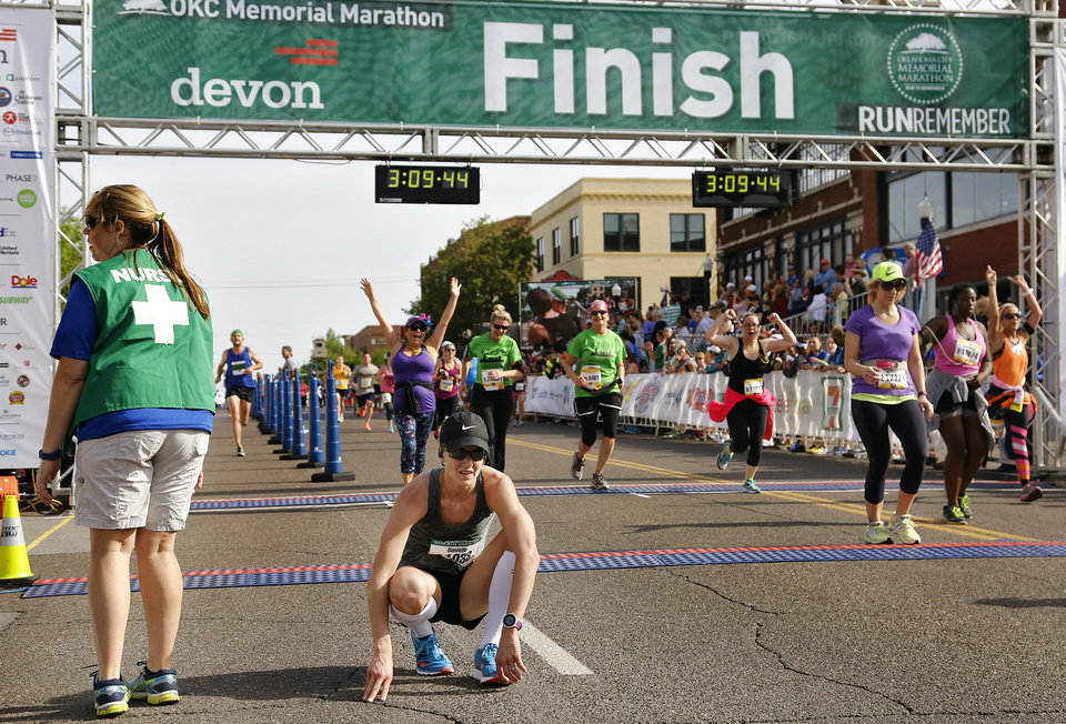 Photo - Danielle Hodge squats down to catch her breath after the photo finish with Catherine Lisle in the women's full marathon during the Oklahoma Memorial Marathon in Oklahoma City, Okla. on Sunday, April 24, 2016.  Hodge finished second in the race.  Photo by Chris Landsberger, The Oklahoman