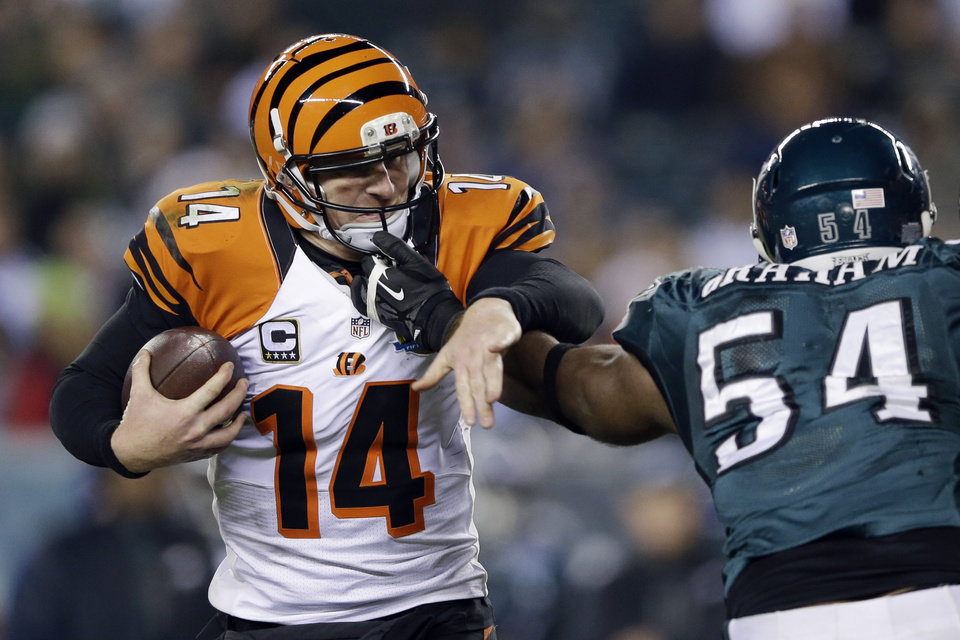 Cincinnati Bengals' Andy Dalton, left, tries to break free from Philadelphia Eagles' Brandon Graham in the second half of an NFL football game, Thursday, Dec. 13, 2012, in Philadelphia. (AP Photo/Matt Rourke)