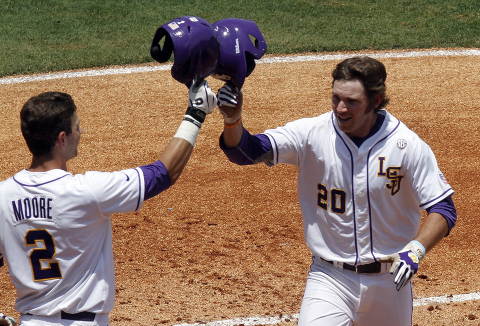Photo - LSU's Conner Hale (20) celebrates with Tyler Moore (2) after hitting a home run against Arkansas during the second inning at the Southeastern Conference NCAA college baseball tournament on Saturday, May 24, 2014, in Hoover, Ala. (AP Photo/Butch Dill)
