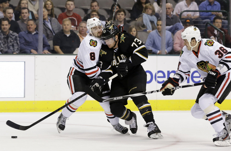 Chicago Blackhawks\' Nick Leddy (8) and center Dave Bolland (36) stop Dallas Stars right wing Michael Ryder (73) from moving the puck to the net in the first period of an NHL hockey game on Thursday, Jan. 24, 2013, in Dallas. (AP Photo/Tony Gutierrez)