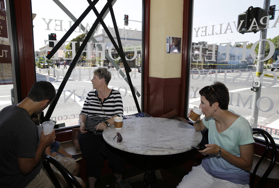 Photo - From left, tourists Colin Norman, his mother-in-law, Agnes Gill, and his wife, Beatrice, all of Vancouver, Canada sit next to an earthquake-damaged window at the Napa Valley Coffe Roasting Company, Monday, Aug. 25, 2014, in Napa, Calif. The San Francisco Bay Area's strongest earthquake in 25 years struck the heart of California's wine country early Sunday, igniting gas-fed fires, damaging some of the region's famed wineries and historic buildings, and sending dozens of people to hospitals. (AP Photo/Eric Risberg)