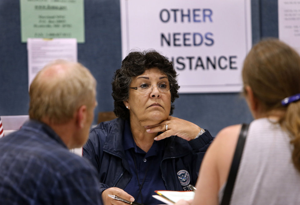 Larry and Denise Morgan get help from FEMA team member Rosalie Toledo, center, at the disaster recovery center at Capitol Hill Baptist Church on Wednesday, July 17, 2013, in Oklahoma City, Okla.  Photo by Steve Sisney, The Oklahoman