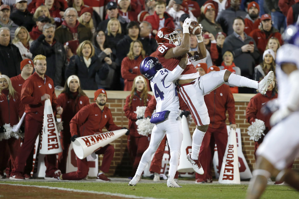 Photo - Oklahoma's Brayden Willis (81) catches a touchdown pass over TCU's Julius Lewis (24) during an NCAA football game between the University of Oklahoma Sooners (OU) and the TCU Horned Frogs at Gaylord Family-Oklahoma Memorial Stadium in Norman, Okla., Saturday, Nov. 23, 2019. [Bryan Terry/The Oklahoman]