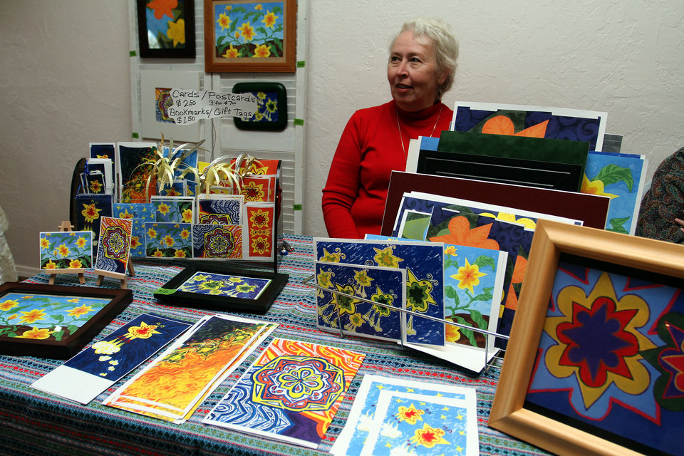Jeanne Flanigan displays her artwork Saturday at the Winter Thyme Art Market at West Wind Unitarian Universalist Congregation in Norman. PHOTO BY HUGH SCOTT, FOR THE OKLAHOMAN