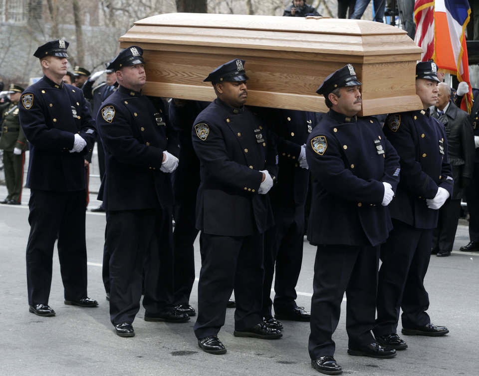 Photo - A casket containing the body of former New York City Mayor Ed Koch is loaded into a hearse while city employees, politicians, media and others look on after his funeral in New York, Monday, Feb. 4, 2013. Koch was remembered as the quintessential New Yorker during a funeral that frequently elicited laughter, recalling his famous one-liners and amusing antics in the public eye. Koch died Friday of congestive heart failure at age 88. (AP Photo/Seth Wenig)