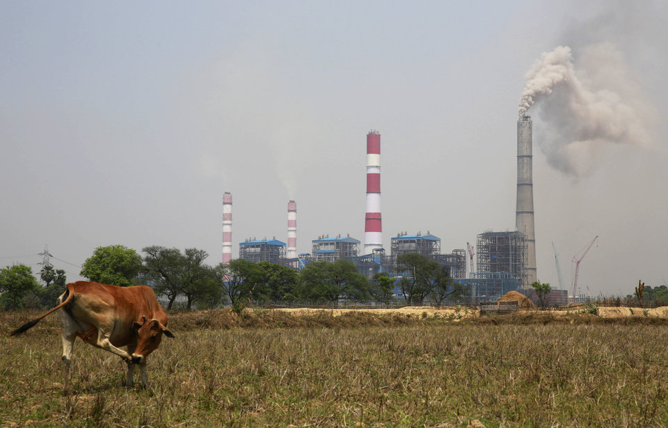 Photo - In this April 15, 2014 photo, smoke emits from an electricity plant owned by Jindal Steel & Power Ltd. that runs on coal gathered from open mines dug near villages in Tamnar, near the industrial city of Raigarh, Chhattisgarh state, India. The company has been mining coal in the area for several years. (AP Photo/Rafiq Maqbool)