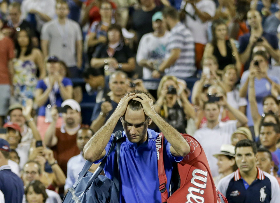Photo - Roger Federer, of Switzerland, walks off the court after losing to Tommy Robredo, of Spain, during the fourth round of the 2013 U.S. Open tennis tournament, Monday, Sept. 2, 2013, in New York. (AP Photo/Darron Cummings)