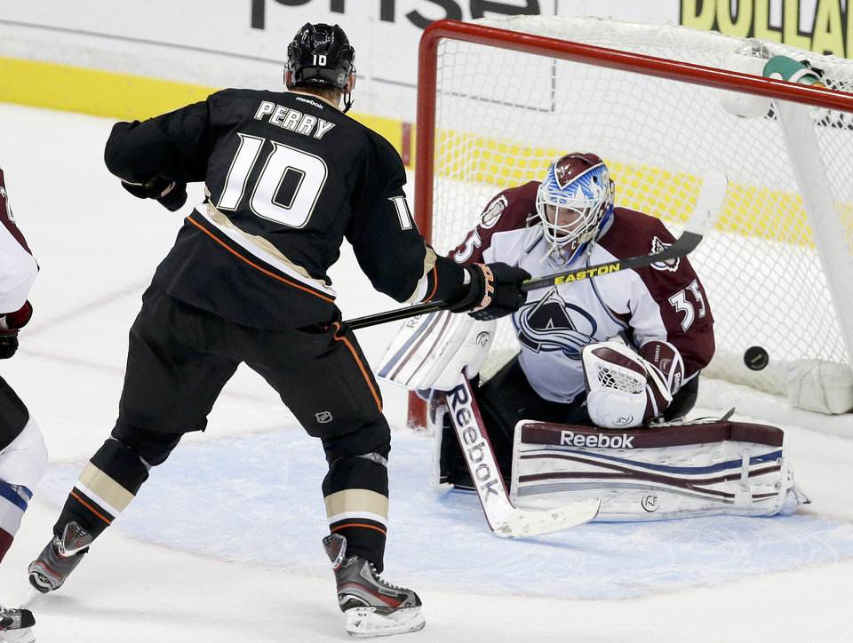 Anaheim Ducks right wing Corey Perry, left, scores the winning goal past Colorado Avalanche goalie Jean-Sebastien Giguere during overtime of an NHL hockey game in Anaheim, Calif. Sunday, Feb. 24, 2013. The Ducks won 4-3. (AP Photo/Chris Carlson)
