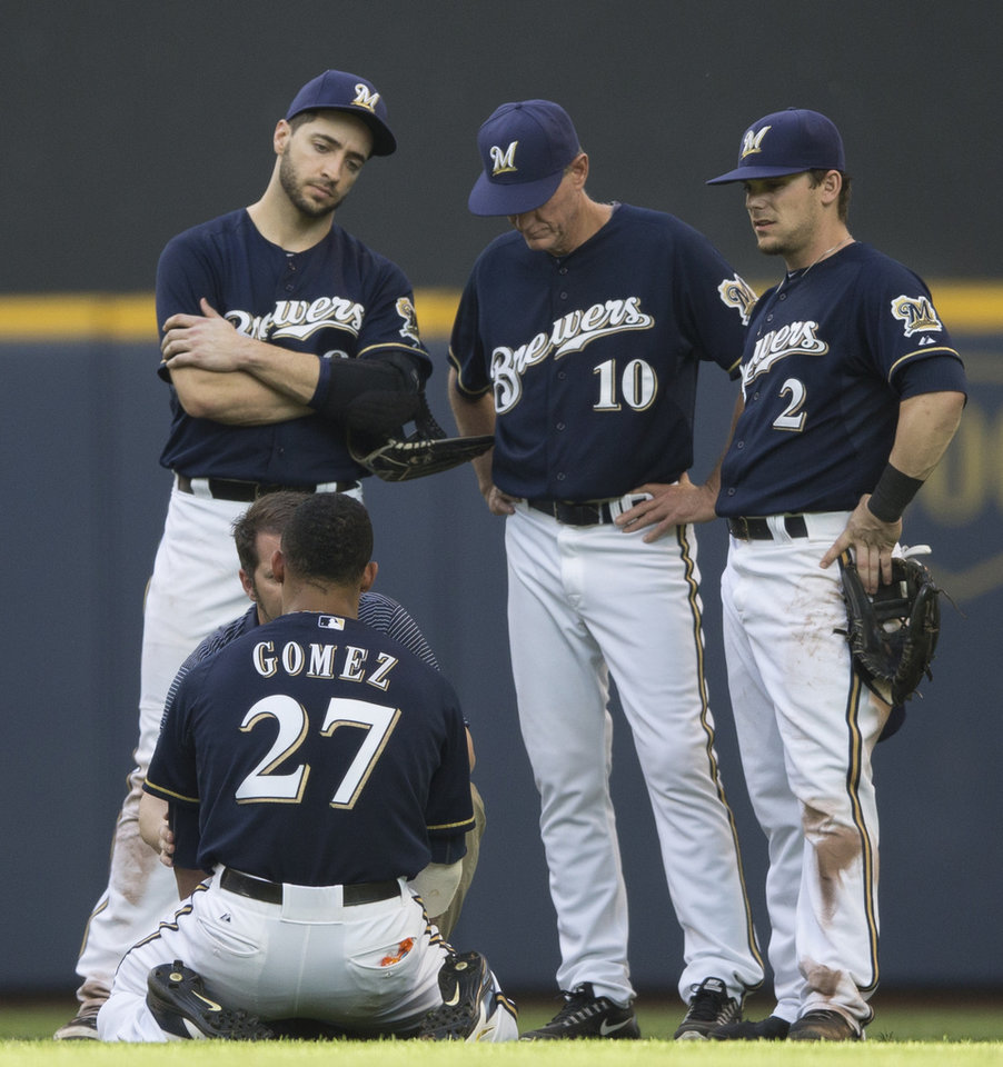 Photo - Carlos Gomez of the Milwaukee Brewers is treated by a member of the training staff after colliding with Ryan Braun in the outfield against the Colorado Rockies during the seventh inning of a baseball game Saturday, June 28, 2014, in Milwaukee. Looking on are teammates Ryan Braun, Scooter Gennett and manager Ron Roenicke.  (AP Photo/Tom Lynn)