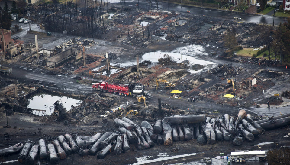 Photo - Workers comb through debris Tuesday, July 9, 2013, after a train derailed Saturday causing explosions of railway cars carrying crude oil in Lac-Megantic, Quebec. (AP Photo/The Canadian Press, Paul Chiasson)