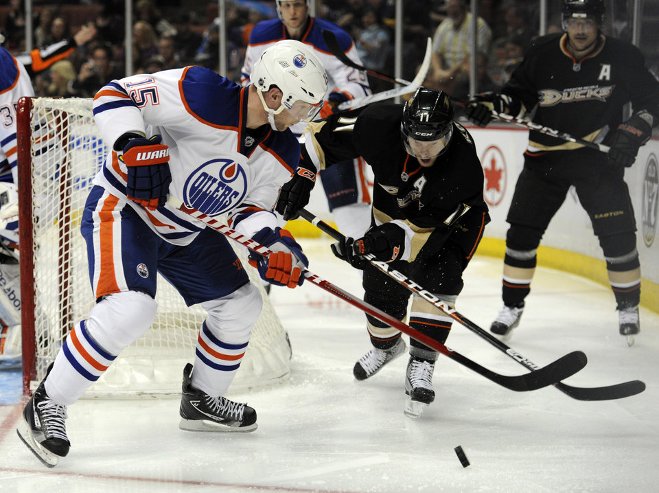 Edmonton Oilers defenseman Nick Schultz (15) keeps the puck away from Anaheim Ducks center Saku Koivu (11), of Finland, in the second period of an NHL hockey game in Anaheim, Calif., Monday, March 5, 2012. (AP Photo/Lori Shepler)