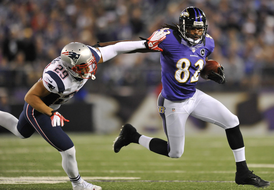 Photo -   Baltimore Ravens wide receiver Torrey Smith, right, rushes the ball past New England Patriots safety Sterling Moore in the second half of an NFL football game in Baltimore, Sunday, Sept. 23, 2012. (AP Photo/Gail Burton)