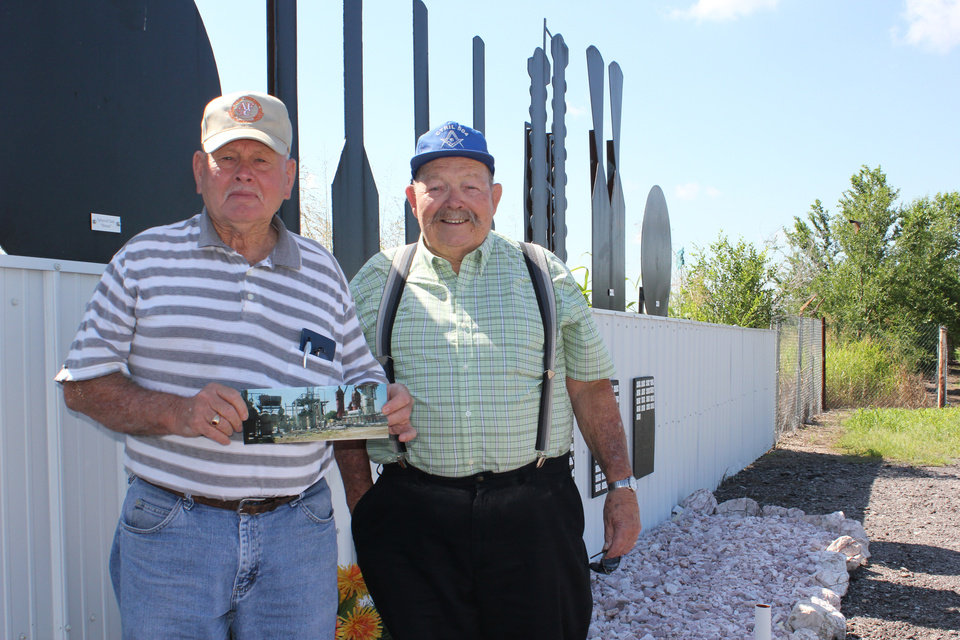 Photo - Val Henery and O.T. Moss stand next to the memorial of the refinery where they each worked for decades. Henery is holding a photograph of the refinery before it was torn down. Hailey Branson-Potts/The Oklahoman