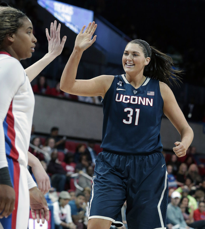 Photo - Connecticut center Stefanie Dolson (31) celebrates with a teammate in front of SMU forward Akil Simpson (5) during the second half of an NCAA college basketball game Tuesday, Feb. 25, 2014, in Dallas. Connecticut won 81-48. (AP Photo/LM Otero)