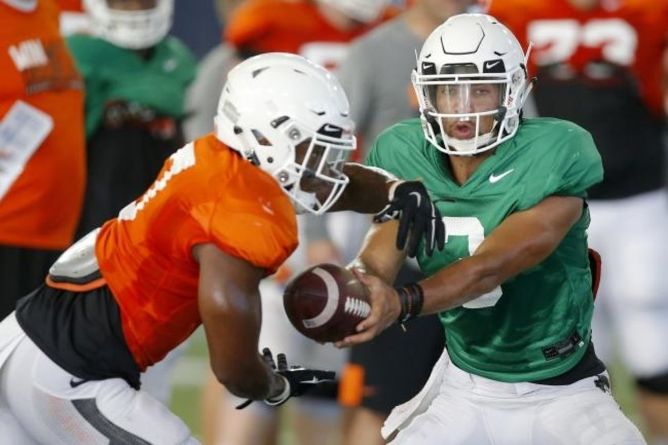 Photo -  Oklahoma State's Spencer Sanders hands the ball off to LD Brown during Tuesday's practice. Spencer and Dru Brown are battling to be the starter, but could platoon to start the season. [Bryan Terry/The Oklahoman]