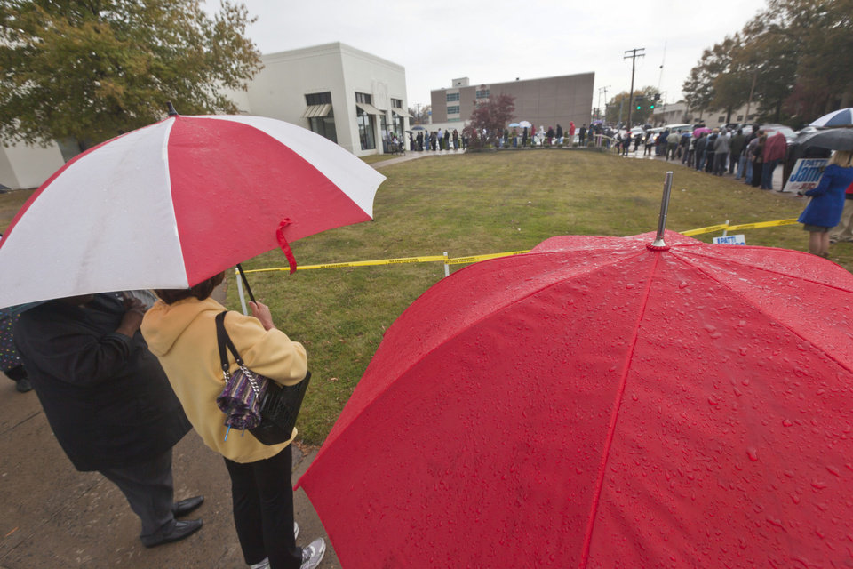 Voters line up in the rain at an early voting poling place in Little Rock, Ark., Monday, Nov. 5, 2012, the last time to vote in advance of the Nov. 6, general election. (AP Photo/Danny Johnston)