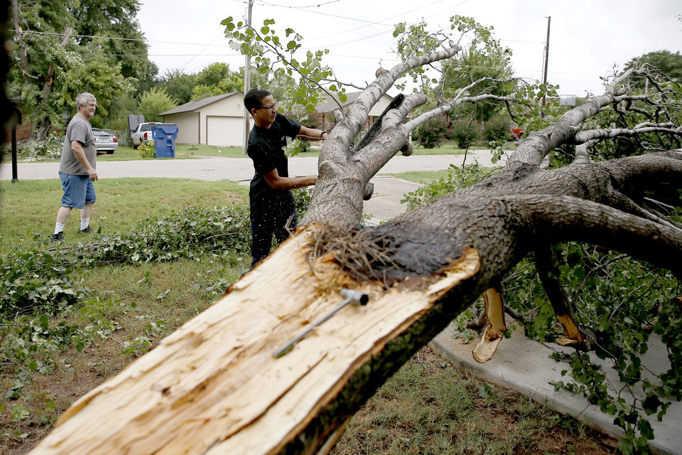 Photo - Randall Johnson watches his son, Darius, 15, cut a damaged tree at their home in Choctaw, Okla., Tuesday, Aug. 27, 2019, after high winds the night before caused damage. [Bryan Terry/The Oklahoman]