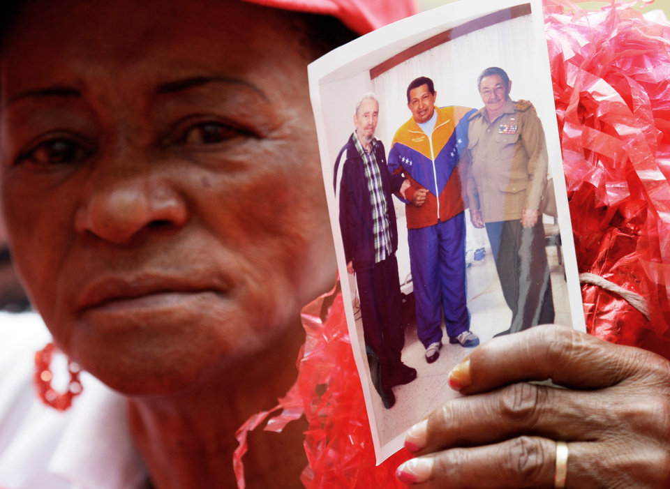 A supporter of Venezuela\'s President Hugo Chavez holds a photo of him, alongside Cuba\'s Raul Castro, right, and Fidel Castro, during a event to commemorate the violent street protests of 1989 known as the