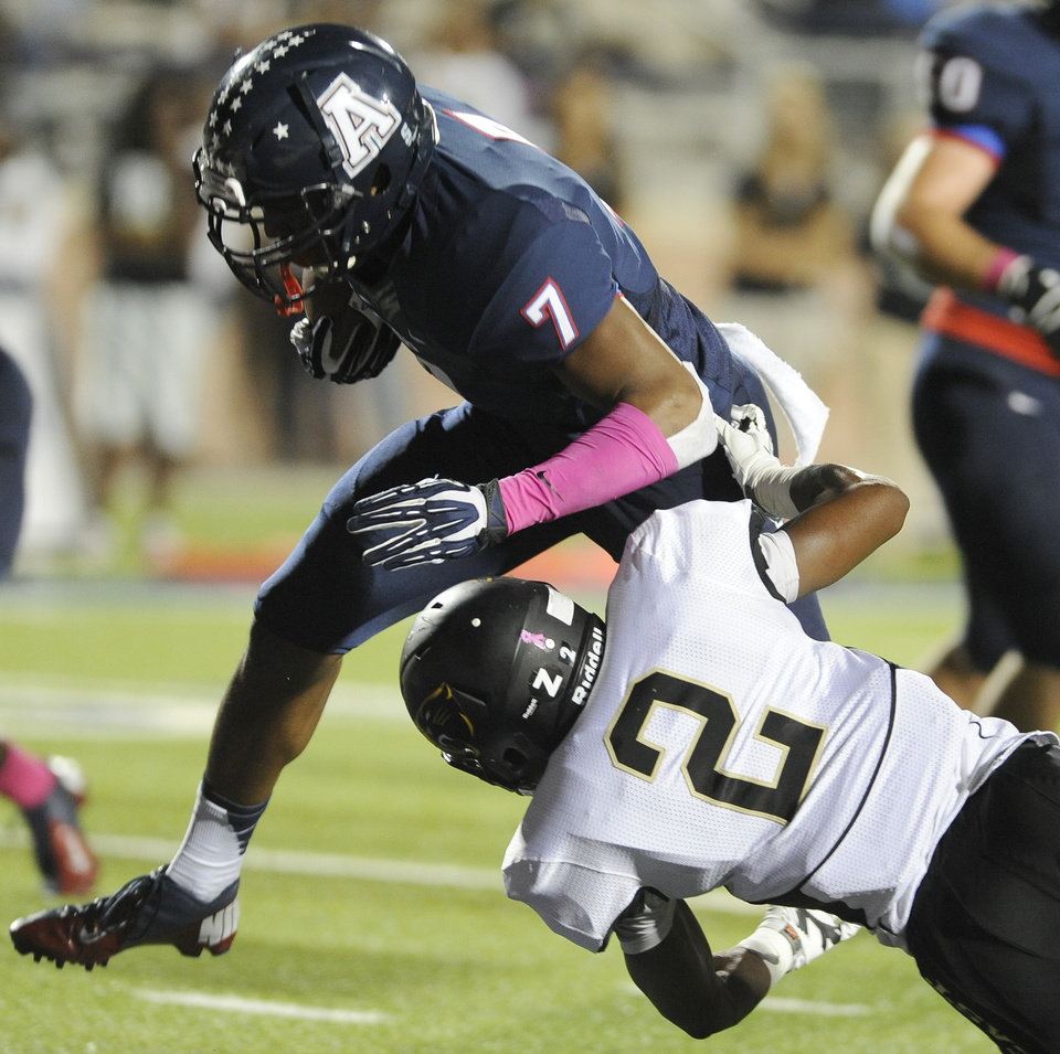 Allen linebacker Tay Evans (7) runs for a first quarter touchdown over Plano East defensive back Ahmad Muhammad (2) during a Class 5A high school football game, Friday, Oct. 11, 2013 at Eagle Stadium in Allen, Texas.  (Matt Strasen/Special Contributor)