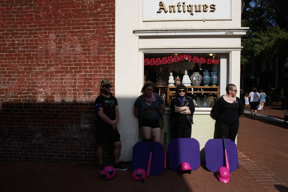 Photo - A group of people who chose not to be identified, stand with shields and bats near the site of a memorial service for Heather Heyer, who was killed during a white nationalist rally, Wednesday, Aug. 16, 2017, in Charlottesville, Va. The group is near the Paramount Theater in case white nationalist show up to protest the service. (AP Photo/Evan Vucci)