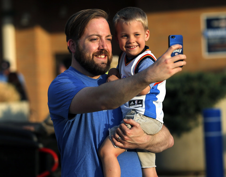Photo - Chris Branson takes a picture with his son Lukas, 3, before Game 1 in the first round of the NBA playoffs between the Oklahoma City Thunder and the Memphis Grizzlies at Chesapeake Energy Arena in Oklahoma City, Saturday, April 19, 2014. Photo by Sarah Phipps, The Oklahoman