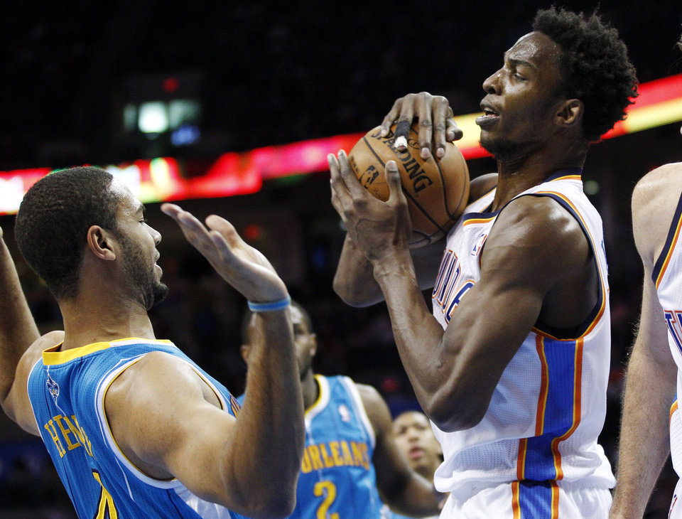 Oklahoma City Thunder center Hasheem Thabeet (34) grabs a rebound in front of New Orleans Hornets guard Xavier Henry in the first quarter of an NBA basketball game in Oklahoma City, Wednesday, Dec. 12, 2012. (AP Photo/Sue Ogrocki)