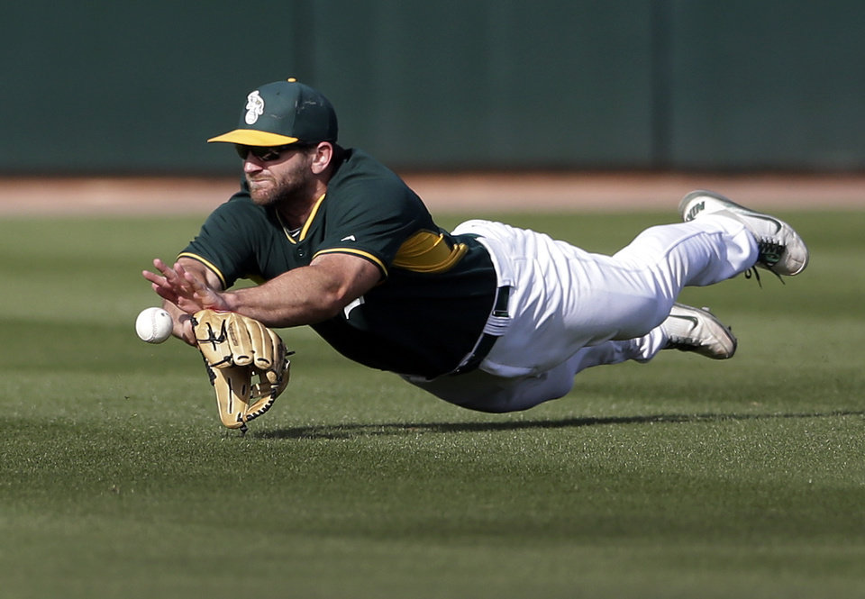 Photo - Oakland Athletics center fielder Shane Peterson can't reach a hit for a single by the Los Angeles Dodgers' Miguel Rojas during the eighth inning of a spring training baseball game Monday, March 3, 2014, in Phoenix. (AP Photo/Gregory Bull)