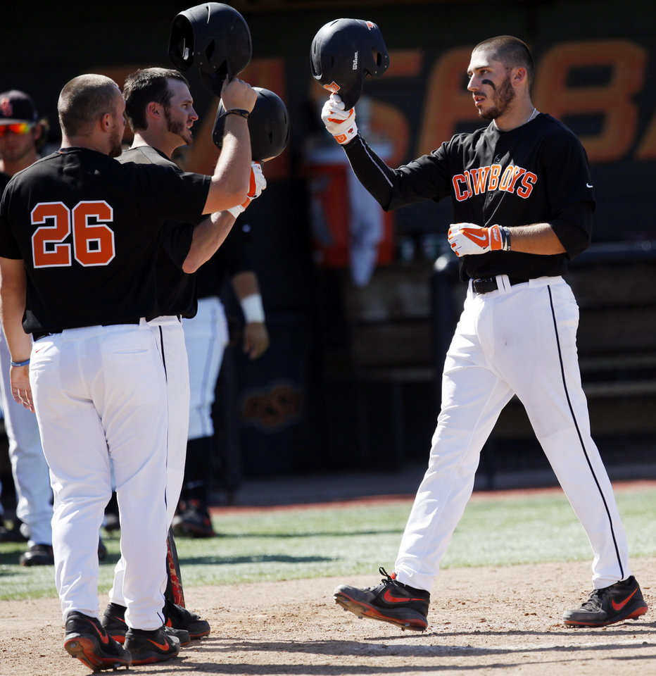 Photo -                    Oklahoma State base runner Tanner Krietemeier, right, is congratulated by teammates after hitting a homerun against Arizona State earlier this month.                                                                             Photo by KT King,                                                          The Oklahoman
