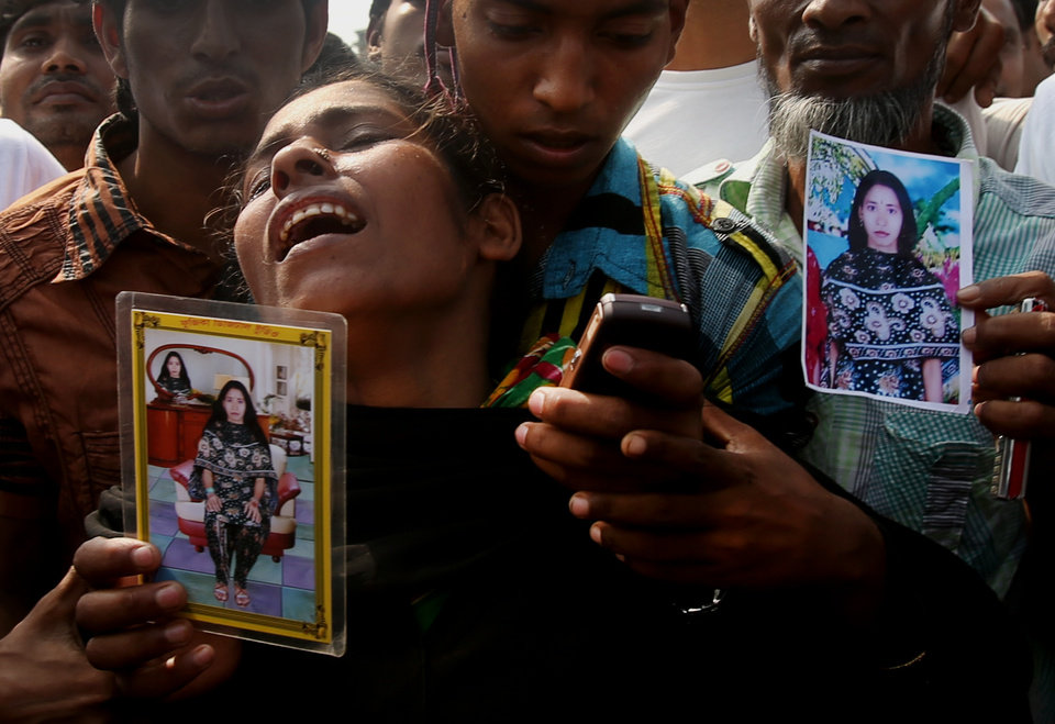 Photo - A woman mourns as she arrived in hopes to find her sister, seen in the photograph she is holding, among unclaimed bodies brought to a cemetery from the garment factory building collapse in preparation for a mass burial on Wednesday May 1, 2013 in Dhaka, Bangladesh. Several hundred people attended a mass funeral in a Dhaka suburb for 18 unidentified workers who died in the building collapse last week last week in the country's worst industrial disaster, killing at least 402 people and injuring 2,500. The bodies, rotting in the spring heat, were brought to the graveyard on the back of a flatbed truck.(AP Photo/Wong Maye-E)