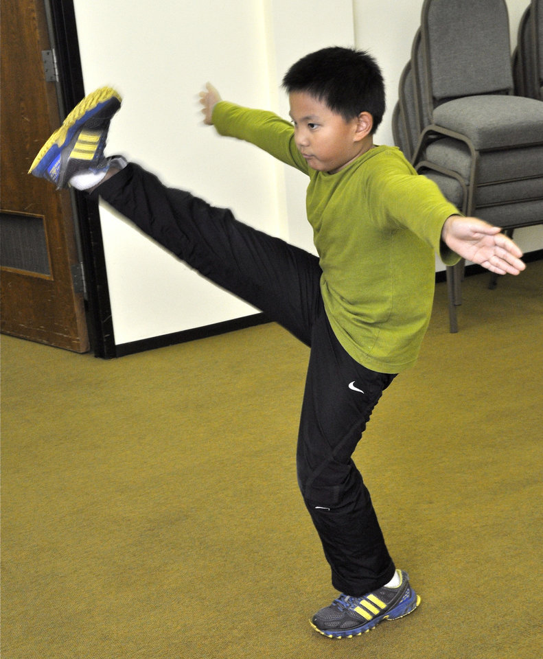 Photo - Sean Wu practices a Kung Fu move during Chinese culture classes at Trinity International Baptist Church. Photo by M. Tim Blake, for The Oklahoman  M. Tim Blake