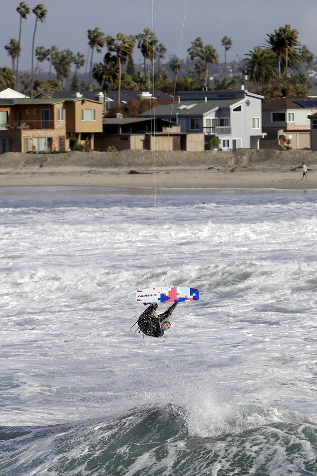 Photo - A kite surfer hangs above large waves Friday, Dec. 11, 2015, in San Diego. Large waves lashed much of the Southern California coastline Friday, prompting the National Weather Service to issue a high surf warning through the weekend. (AP Photo/Gregory Bull)