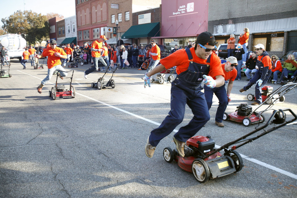Photo - The OSU Lawnmower Drill Team performs in the Oklahoma State Cowboy's homecoming parade in downtown Stillwater, OK, Saturday, Oct. 29, 2011. By Paul Hellstern, The Oklahoman