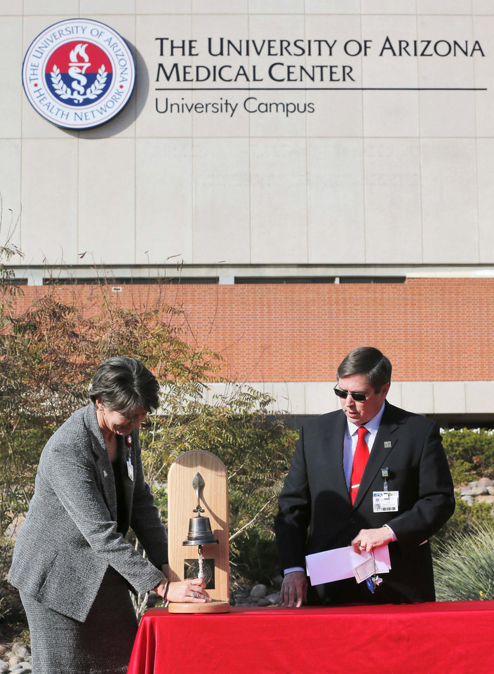 Photo - Karen Mlawsky, CEO of the University of Arizona Medical Center Hospital Division, rings a bell 19 times in honor of the 19 shooting victims during a remembrance ceremony on the third anniversary of the Tucson shootings, Wednesday, Jan. 8, 2014, in Tucson, Ariz. as Chaplin Joe Fitzgerald looks on. Six people were killed and 13 wounded, including U.S. Rep. Gabrielle Giffords, D-Ariz., in the shooting rampage at a community event hosted by Giffords in 2011.  Jared Lee Loughner was sentenced in November 2012 to seven consecutive life sentences, plus 140 years, after he pleaded guilty to 19 federal charges in the shooting. (AP Photo/Matt York)
