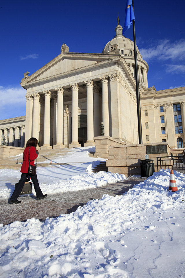 Photo - A pedestrian walking the path shoveled between snow drifts to the south entrance of the state Capitol in Oklahoma City Thursday, Feb. 3, 2011. Photo by Paul B. Southerland, The Oklahoman