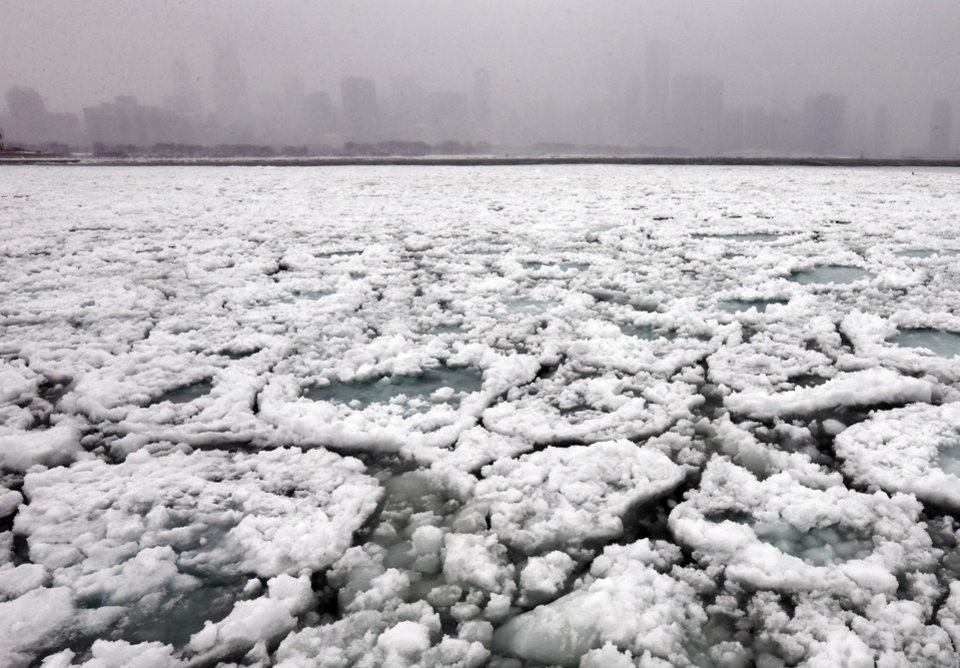 Photo - The Chicago skyline and a freezing Lake Michigan are seen from the Museum Campus in Chicago on Sunday, Jan. 5, 2014. Sunday night temperatures will drastically drop to about minus 20 degrees. (AP Photo/Nam Y. Huh)