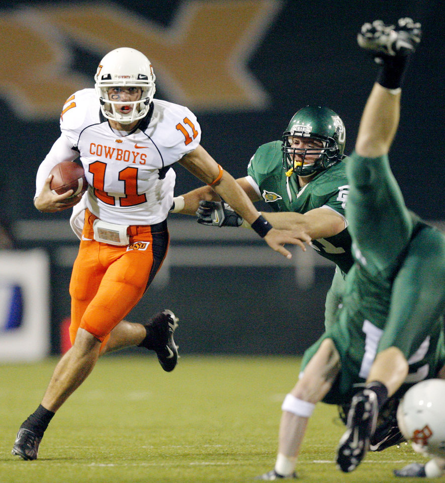 OSU quarterback Zac Robinson (11) scrambles past Baylor\'s Joe Pawelek, center, and Jordon Lake, right, in the first half during the college football game between Oklahoma State University and Baylor University at Floyd Casey Stadium in Waco, Texas, Saturday, Nov. 17, 2007. BY MATT STRASEN, THE OKLAHOMAN
