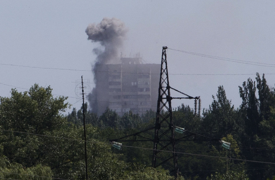 Photo - Smoke from shelling rises over a residential apartment house in Shakhtarsk, Donetsk region, eastern Ukraine on Monday, July 28, 2014. An international police team abandoned its attempt to reach the crash site of a Malaysia Airlines plane for a second day running Monday as clashes raged in a town on the road to the area.(AP Photo/Dmitry Lovetsky)