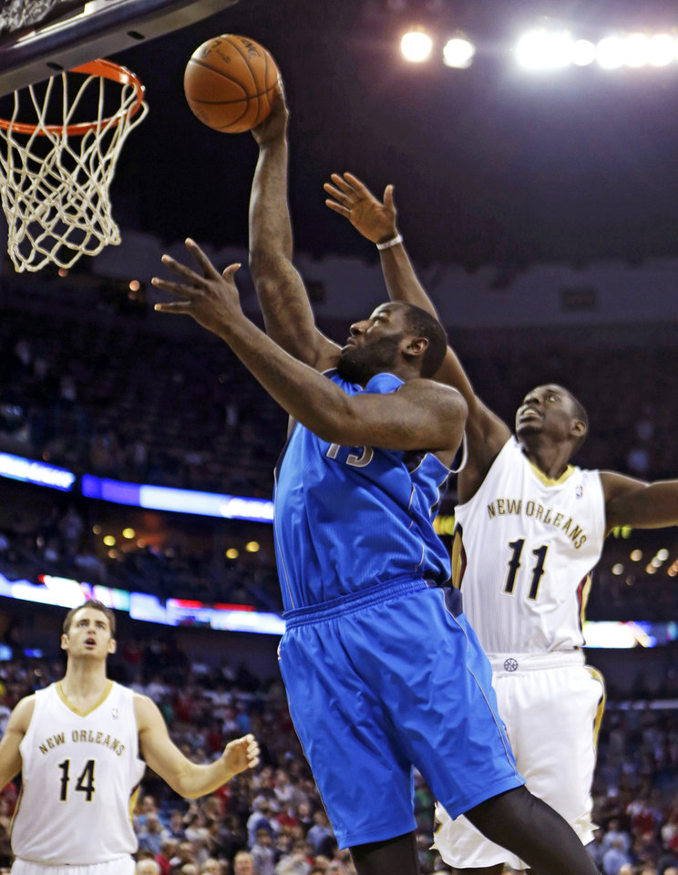 Photo - Dallas Mavericks center DeJuan Blair (45) drives to the basket between New Orleans Pelicans point guard Jrue Holiday (11) and center Jason Smith (14) in the first half of an NBA basketball game in New Orleans, Wednesday, Dec. 4, 2013. (AP Photo/Gerald Herbert)