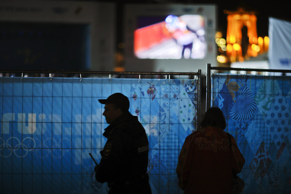 Photo - A police officer patrols next to a 2014 Winter Olympics Live Site broadcasting Olympic coverage on a giant monitor for the public, Saturday, Feb. 15, 2014, in central Sochi, Russia. (AP Photo/David Goldman)