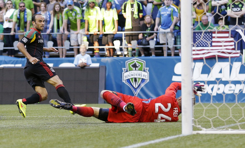 Photo - Los Angeles Galaxy's Landon Donovan, left, scores a goal on Seattle Sounders goalkeeper Stefan Frei, right, in the first half of an MLS soccer match, Monday, July 28, 2014, in Seattle. (AP Photo/Ted S. Warren)