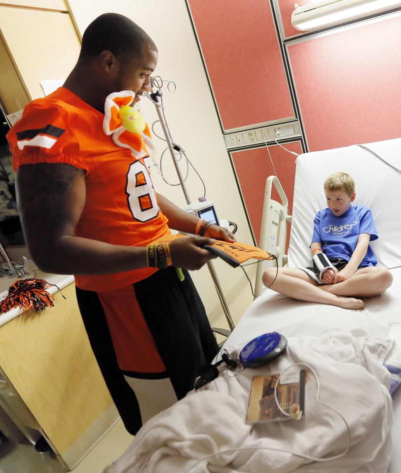 Oklahoma State wide receiver Tracy Moore gives Ernest Cobb, 9, an OSU pack during a visit by OSU football players to The Children's Hospital in Oklahoma City, Wednesday, July 11, 2012. Cobb is a patient at The Children's Hospital. Photo by Nate Billings, The Oklahoman