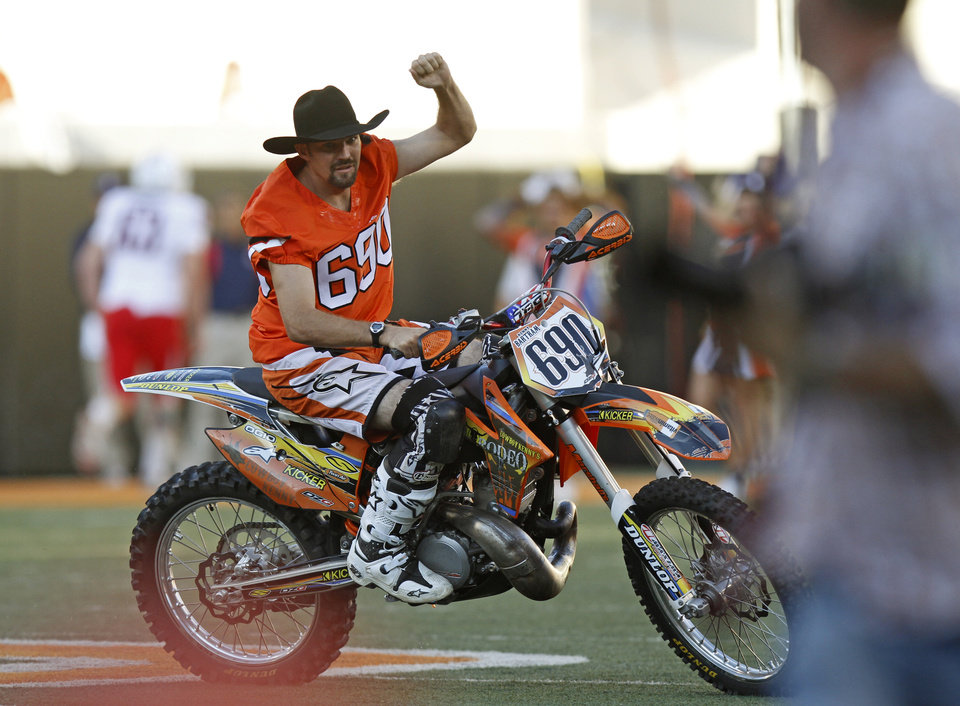 "Professional freestyle motocross star ""Cowboy"" Kenny Bartram rides off the field before Oklahoma State's game against Arizona. Bartram performed before the game with former Oklahoma State golfer Rickie Fowler. PHOTO BY BRYAN TERRY, The Oklahoman"