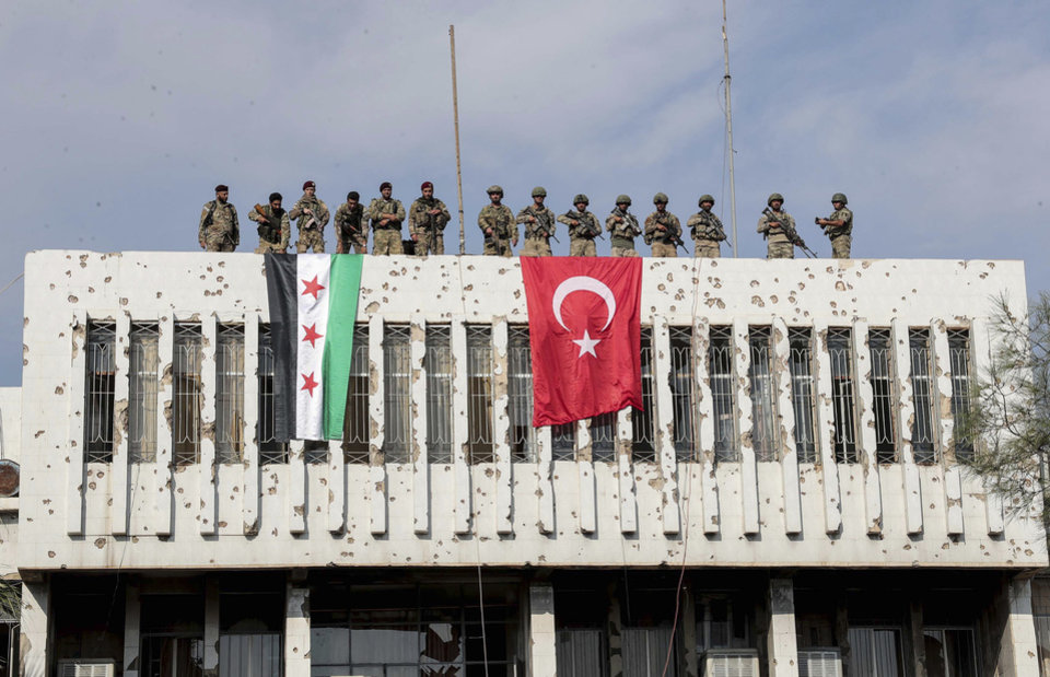 Photo -  Turkish soldiers, right, and Turkey-backed opposition fighters stand atop a building next to their flags in Syrian town of Ras al Ayn, northeastern Syria, Wednesday, Oct. 23, 2019. Turkish media reports say Turkish troops and their allied Syrian opposition forces are securing a town in northeast Syria after Syrian Kurdish fighters pulled out of the area.(Ugur Can/DHA via AP)