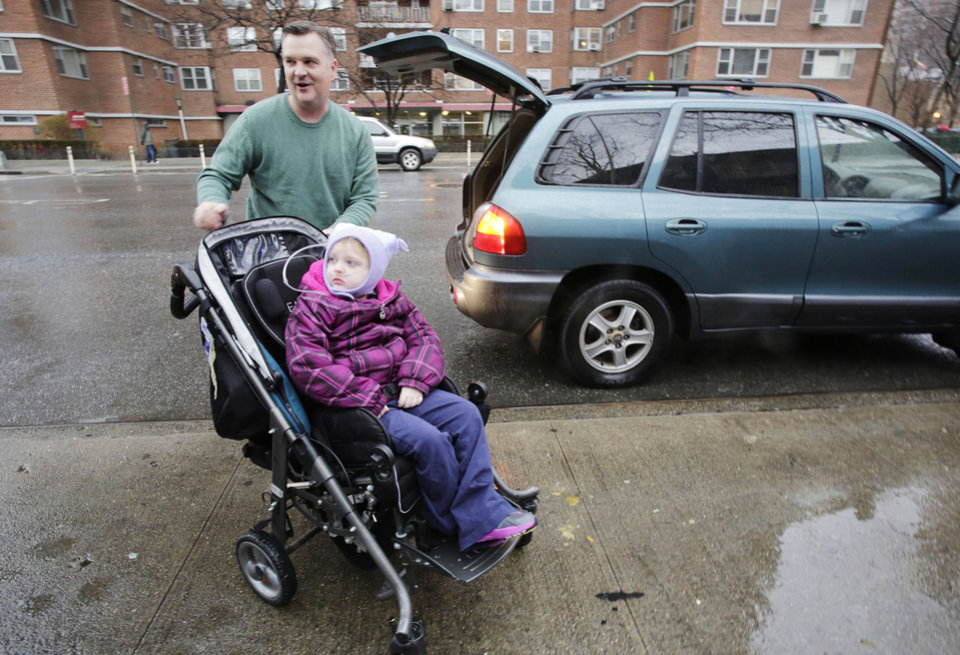 Photo - Peter Curry pushes his daughter Maisy, 7, in her wheel chair after driving her to Public School 33, Wednesday, Jan. 16, 2013 in New York. Maisy Curry would normally be driven by school bus, according to her father. More than 8,000 New York City school bus drivers and aides went on strike over job protection Wednesday morning, leaving some 152,000 students, many disabled, trying to find other ways to get to school. (AP Photo/Mark Lennihan)