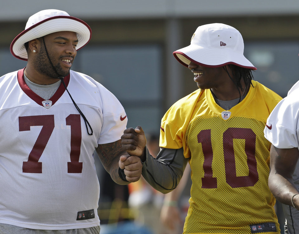 Washington Redskins tackle Trent Williams (OU) (71) and quarterback Robert Griffin III (10) walk out for the morning practice at the NFL football teams training camp in Richmond, Va. Tuesday, July 30, 2013.   (AP Photo/Steve Helber)