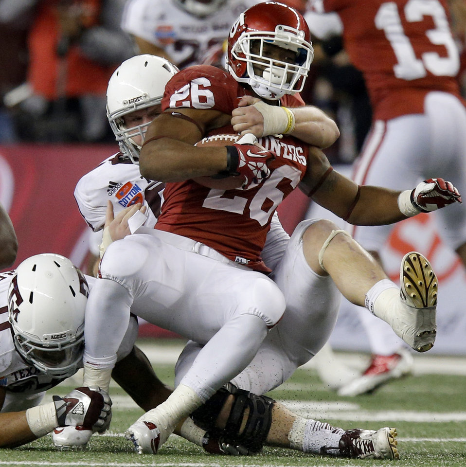 Photo - Oklahoma's Damien Williams (26) is brought down by Texas A&M 's Spencer Nealy (99) during the Cotton Bowl college football game between the University of Oklahoma (OU)and Texas A&M University at Cowboys Stadium in Arlington, Texas, Friday, Jan. 4, 2013. Oklahoma lost 41-13. Photo by Bryan Terry, The Oklahoman