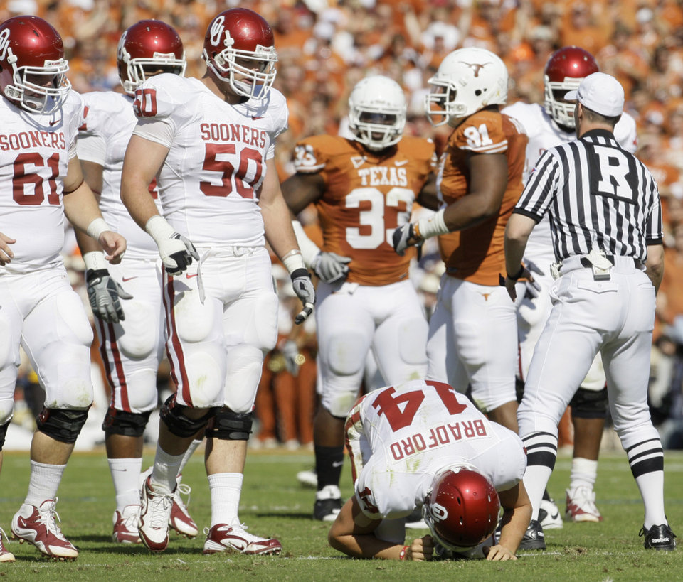 Photo - Sam Bradford stays on the ground after getting injured in the first quarter of OU's 16-13 loss to Texas. AP Photo