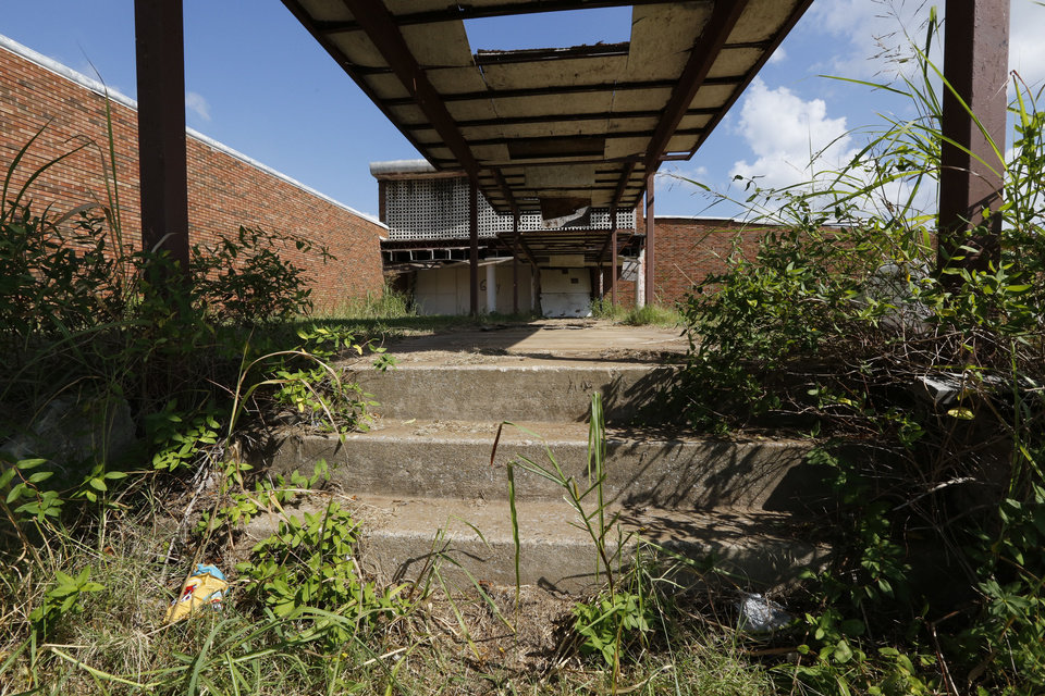 Photo -  Weeds grow high around the Bryant Center, one of hundreds of abandoned properties that Oklahoma City officials must deal with.