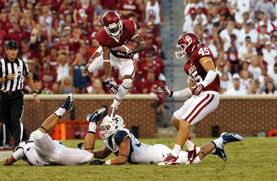 Photo - Oklahoma's Jalen Saunders (8) leaps over tacklers on a punt return during a college football game between the University of Oklahoma Sooners (OU) and the West Virginia University Mountaineers at Gaylord Family-Oklahoma Memorial Stadium in Norman, Okla., on Saturday, Sept. 7, 2013. Photo by Steve Sisney, The Oklahoman